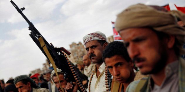 A Shiite Houthi rebel holds his weapon as he attends a rally to protest Saudi-led airstrikes, in Sanaa,...