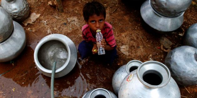 An Indian boy drinks water collected from a government water supply tap at an impoverished settlement...