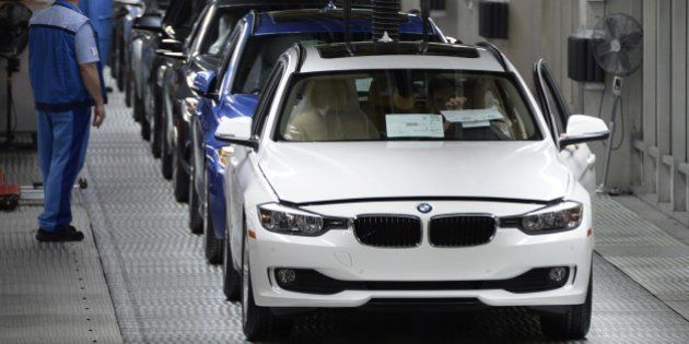 Employees of German car maker BMW work on an assembly line for BMW cars at the company's plant in Munich,...