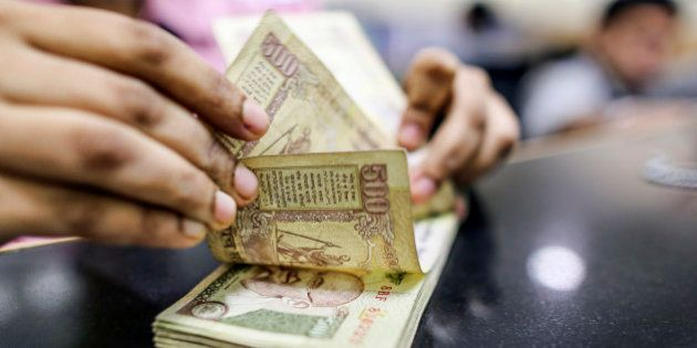 An employee counts Indian five-hundred rupee banknotes for a photograph at a branch of the HDFC Bank...
