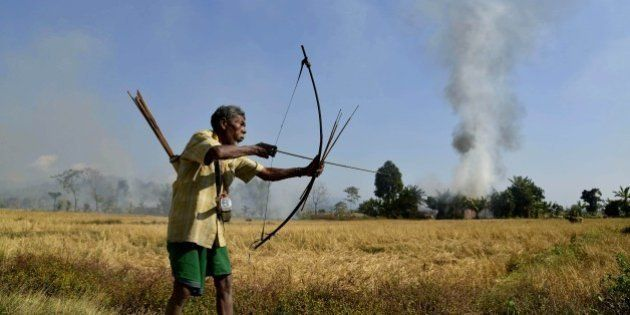 Indian tribal villager or Adivasi stands with a bow and arrow as homes burn in the village of Tenganala...