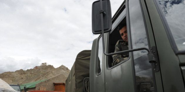 An Indian soldier sits in one of the army trucks used to transport government-provided relief materials...
