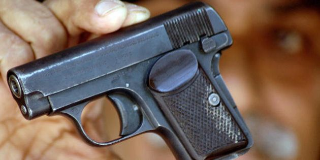 Hyderabad, INDIA: Indian gun enthusiast Omim Debara holds a pistol, one of his licenced guns at his home...