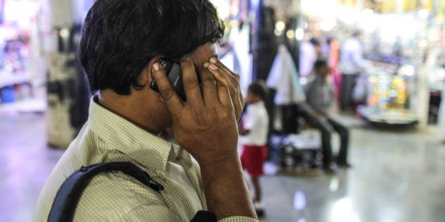 A man reacts while talking on a Karbonn Mobiles India Pvt. phone outside Chhatrapati Shivaji Terminus...
