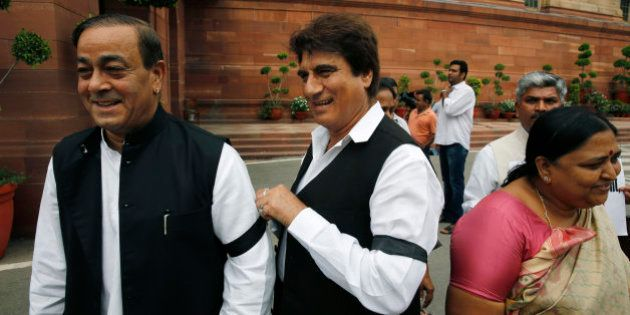 A Congress party lawmaker ties a black band on his colleague's hand during a protest in the Parliament...