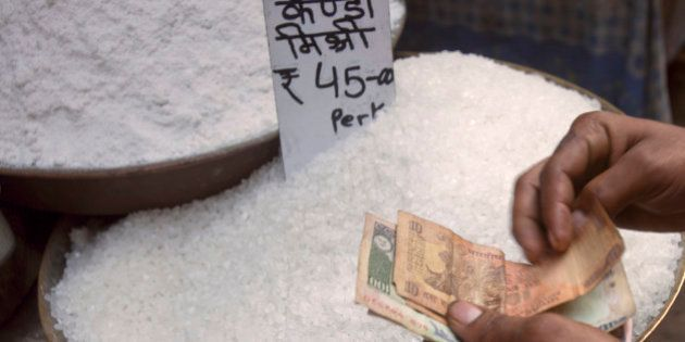 A customer counts Indian rupee bank notes over a tray of sugar at a wholesale market in the Old Delhi...