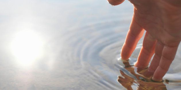 Person touching surface of lake water (focus on