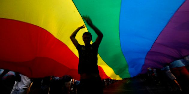 A gay rights activist dances under a rainbow flag during the Gay Pride parade in downtown Athens, on...