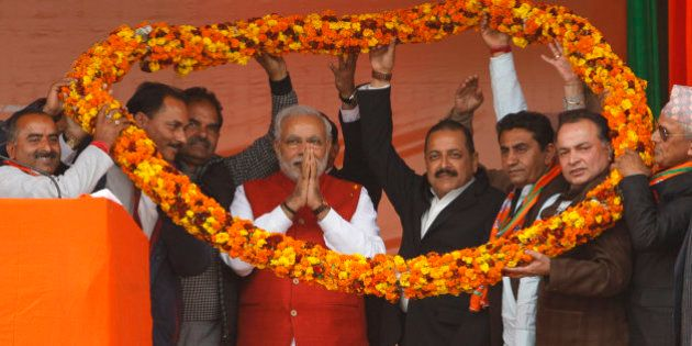 India's ruling Bharatiya Janata Party (BJP) supporters hold a giant floral garland around Prime Minister...