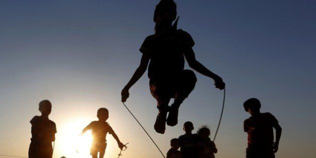Iraqi displaced children play at sunset at a temporary camp set up to shelter people fleeing violence...