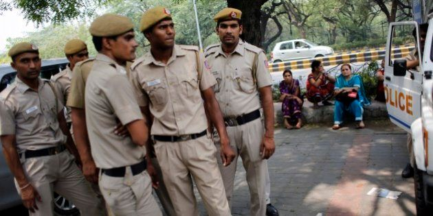 Delhi policemen stand guard as members of All India Democratic Women's Association (AIDWA) sit on a pavement...