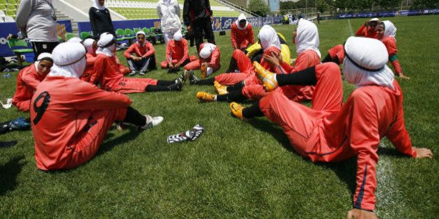 Players of Iran's women national football team listen to instructions before their friendly football...