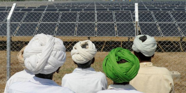 Indian villagers look at solar panels during the inauguration of a solar farm in the village of Gunthawada,...