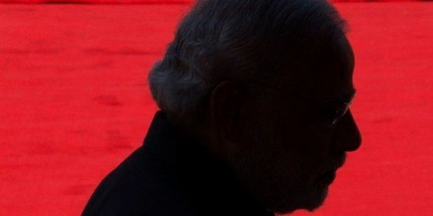 Indian Prime Minister Narendra Modi is silhouetted as he walks on the red carpet during the ceremonial...