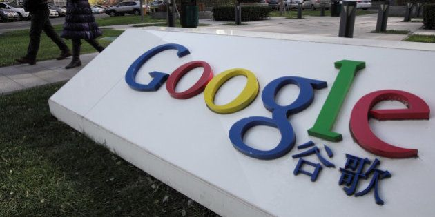 Pedestrians walk past the Google Inc. logo displayed outside the building housing the company's China...