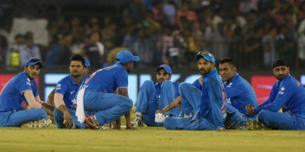 India's captain Mahendra Singh Dhoni (2R) sits with teammates as play is interrupted by spectators throwing...