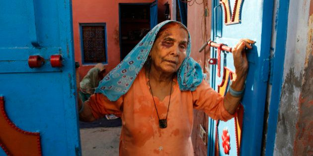 A bruised Asgari Begum, mother of 52-year-old Muslim farmer Mohammad Akhlaq, stands by the entrance of...