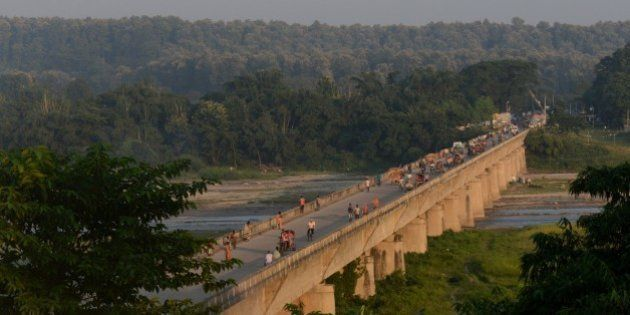 People walk over a bridge at an entry point to Nepal from India at Mechinagar on the eastern Nepalese...