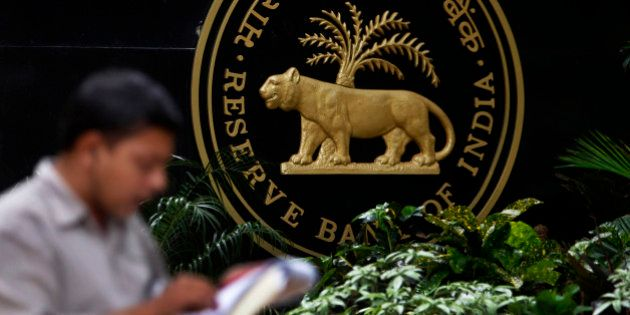 A media person speaks on phone next to the logo of the Reserve Bank of India (RBI) in Mumbai, India,...