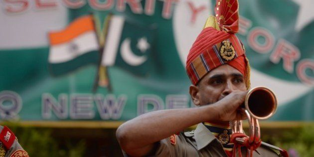 An Indian Border Security Force (BSF) ceremonial guard blows a bugle during a reception for Pakistan...