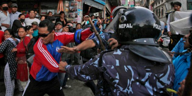 Nepalese protesters try to clash with policemen after burning a copy of the new constitution during the...