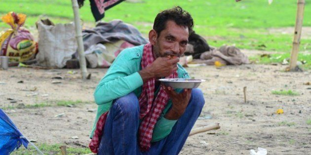ALLAHABAD, UTTAR PRADESH, INDIA - 2015/07/15: An Indian homeless man eats food in front of his shelter...