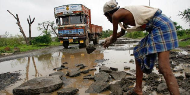 Mumbai, INDIA: An Indian labourer repairs a stretch of damaged road in Mumbai, 09 July 2007. The city...