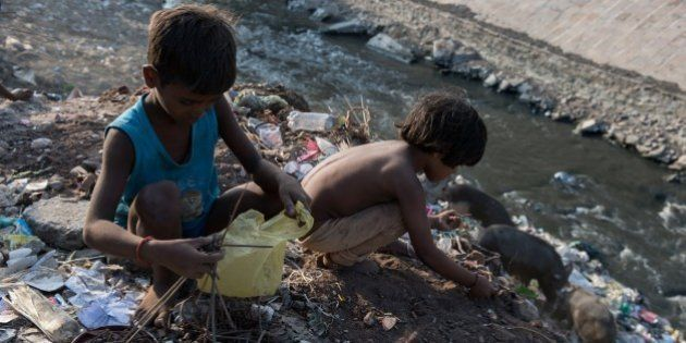 Indian boys Chandan (L), 6, and Badar, 5, sort through waste on the banks of a small polluted tributary...