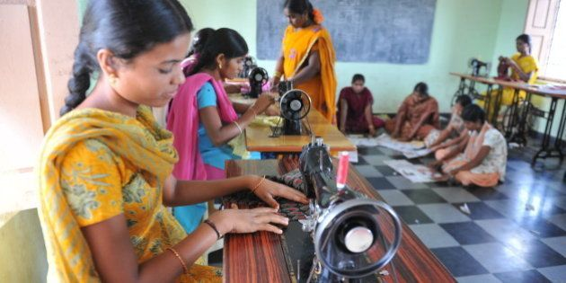 Indian rural women use sewing machines at the Mother Teresa Rural Development Society centre at Narketpally...