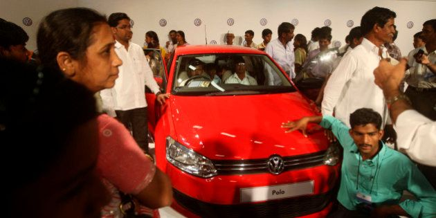 People take a closer look of a Volkswagen Polo at its new factory in Chakan, near Pune, India, Saturday,...