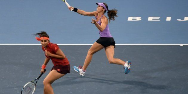 Martina Hingis (top) of Switzerland hits a return as she partners Sania Mirza of India during their second...