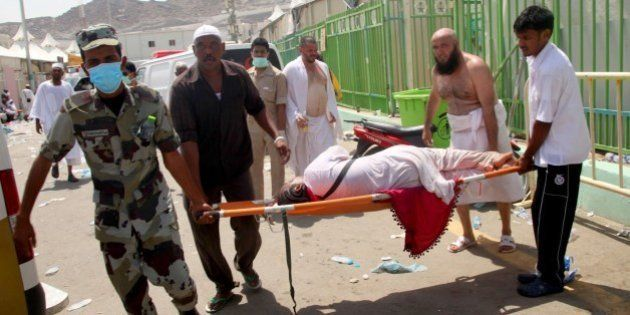 Hajj pilgrims and Saudi emergency personnel carry a woman on a stretcher at the site where at least 450...