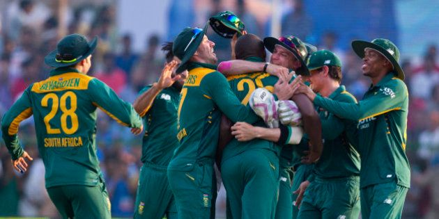 South African cricketers surround Kagiso Rabada, center, who took crucial wickets of India to swing the...
