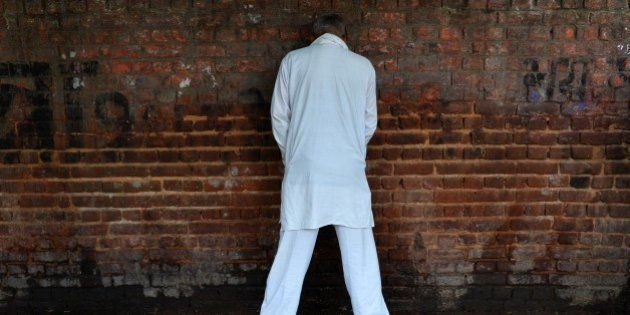 An Indian man urinates on a wall in New Delhi on November 18, 2014, the eve of World Toilet Day. UNICEF...