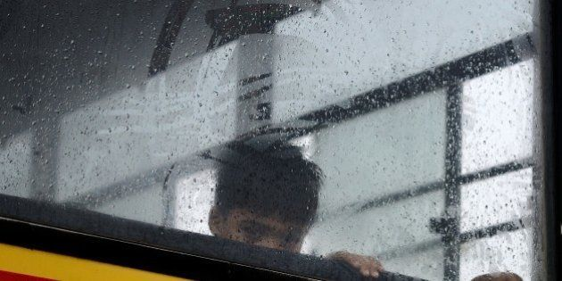 An Indian child looks out from his school bus in Faridabad on the outskirts of New Delhi on July 9, 2015,...
