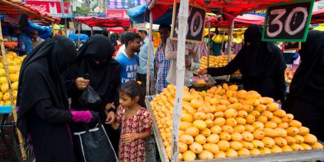 HYDERABAD, TELANGANA, INDIA - 2015/06/21: Muslim women in burqa buy fruits near Charminar during the...