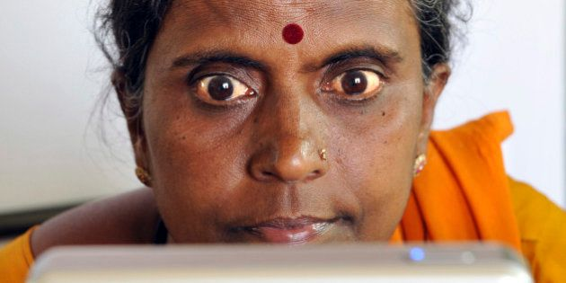 An Indian villager opens up her eyes for iris scanning infront of an Iris Access machine during the data...