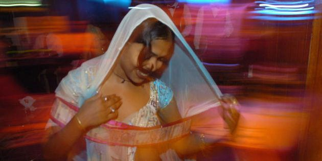 MUMBAI, INDIA: In this picture taken late 06 May 2005, An Indian bar dancer dances with a garland of...