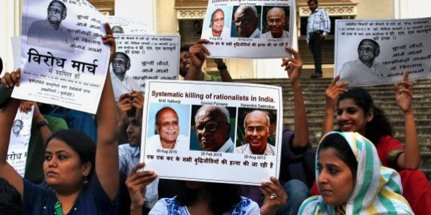 People hold placards during a protest against the killing of scholar M.M. Kalburgi in Mumbai, India,...
