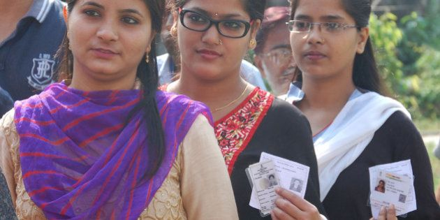 BHAGALAPUR, INDIA - OCTOBER 12: Voters pose with their cards for picture as they wait in a long queue...
