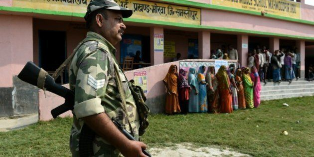 Indian voters queue to cast their ballots as security personnel stand guard at a voting centre in the...