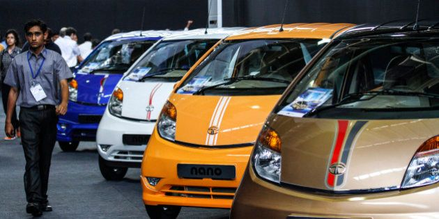 An employees walk past a line of Tata Motors Ltd. Nano automobiles on display during a media event in...