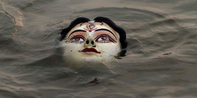 An idol of Hindu goddess Durga floats in water as devotees immerse the same in the River Kuakhai after...