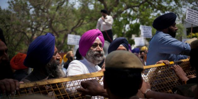 Indian Sikhs stand near a police barricade during a protest against Congress party leader and former...