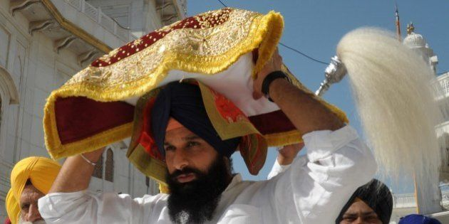 Indian Punjab Revenue Minister Bikram Singh Majithia (C) carries the Guru Granth Sahib (Sikh holy book...