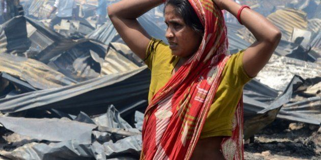 An Indian resident stands in front of the charred remains of her damagaed home after a fire broke out...