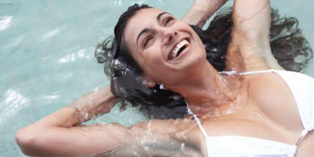 Young woman floating in sea, hands behind head, laughing,