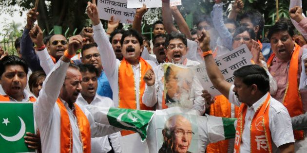 Hindu right-wing Shiv Sena activists burn an effigy and pictures of Pakistani Prime Minister Nawaz Sharif,...