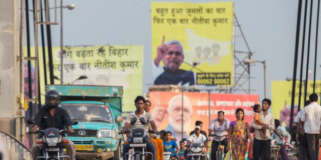People ride motorcycles over a bridge past election billboard advertisements featuring images of Indian...