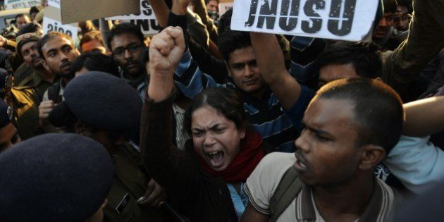 Indian residents hold placards and chant slogans as they take part in a protest against the alleged rape...